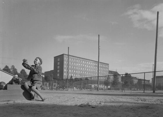 Taustalla Helsinign Aleksis Kiven kansakoulu, etualalla tyttö leikkikentällä.