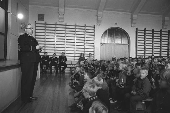 Poliisi puhuu voimistelusalissa istuville koululaisille.