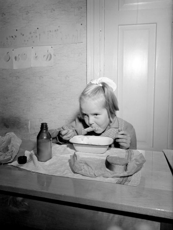 Ruokatunti kansakoulussa. Tyttö syö kulhosta, vieressä maitopullo ja eväsleipää.