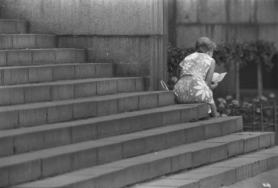 Nainen istuu aseman portailla tarkastellen karttaa, 1960-luku.
