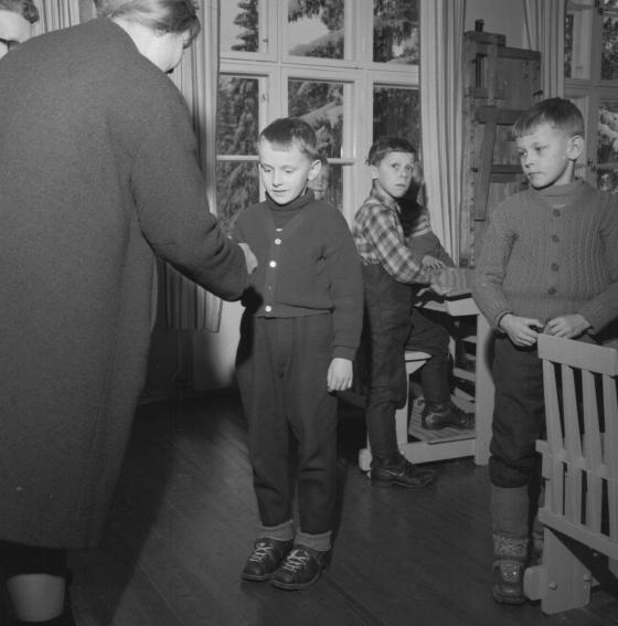 Koululaiselle ojennetaan luokassa jokin palkinto. Kalle Kultala, 1960-luku.