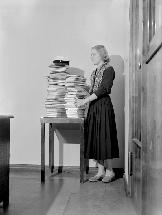 Ylioppilas seisoo lukiossa lukemiensa kirjojen äärellä. Kalle Kultala, 1952.