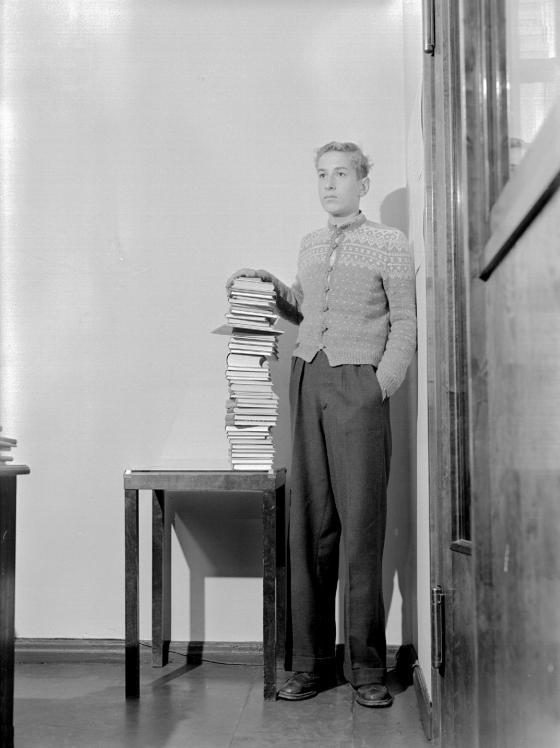 Keskikoulun käynyt nuori mies seisoo keskikoulun aikana luetun kirjapinon viere
