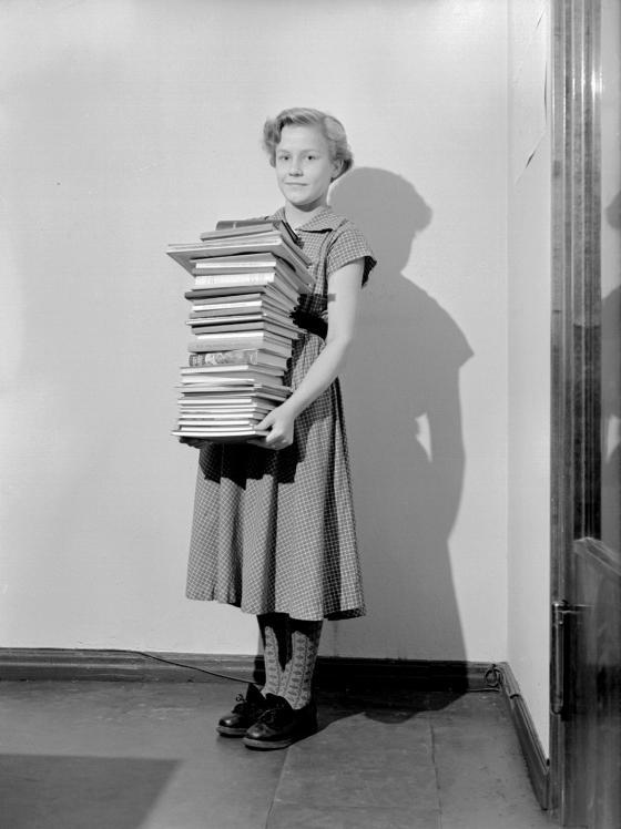 Kansakoulun käynyt nuori nainen sylissään kouluaikana lukemansa kirjat. Kalle Ku