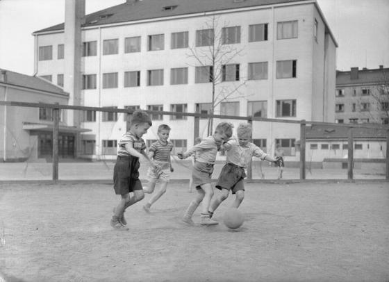 Pojat potkivat jalkapalloa koulun pihalla. Kalle Kultala, 1950-luku.