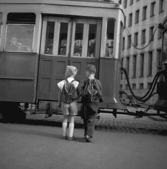 Kaksi reppuselkäistä koulupoikaa odottamassa raitiovaunun vierellä.