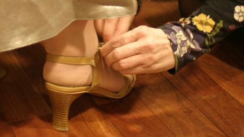 Puvustaja auttaa kenkien sovituksessa. Kuva: YLE
